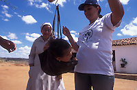 """Fight against infant malnutrition - NGO """"Pastoral da Criança"""" (Child Pastoral) agents monitor children´s weight with a scale in the rural area of region affected by drought with several cases of undernourishment. Brejinho municipality, Pernambuco State, northeastern Brazil."""