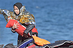 A refugee woman clutches her baby after landing on a beach near Molyvos, on the Greek island of Lesbos, on November 2, 2015. Part of a boatful of refugees that arrived from Turkey, she and her family were received by local and international volunteers, then proceeded on their way toward western Europe. The boat was provided by Turkish traffickers to whom the refugees paid huge sums to arrive in Greece.