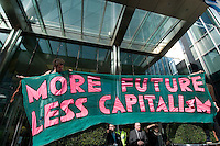 'More future, less capitalism' - Climate Camp protestors put up a banner outside Barclays Bank in Canary Wharf, London, the latest in a series of protests organised by Camp for Climate Action calling for a carbon-neutral society.