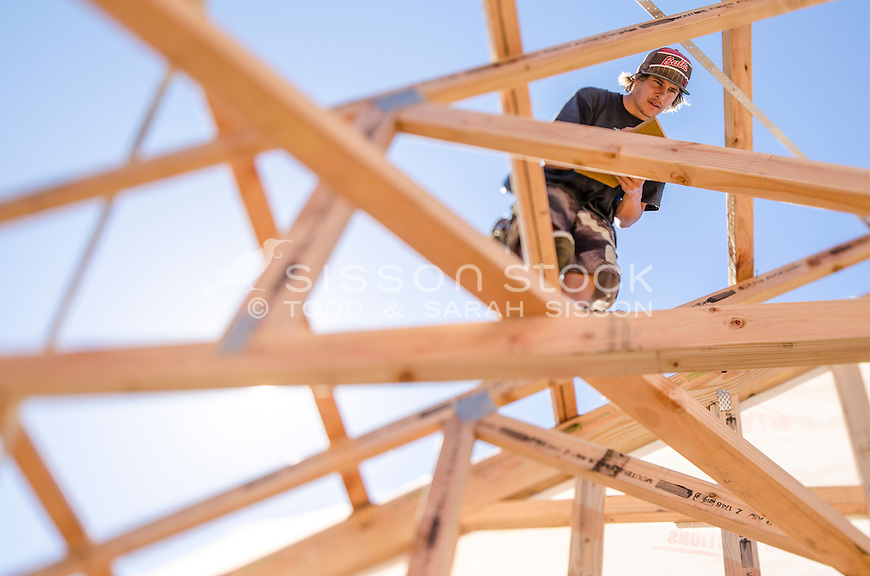 Looking through new timber house framing up to roofer and blue sky, New Zealand - stock photo, canvas, fine art print