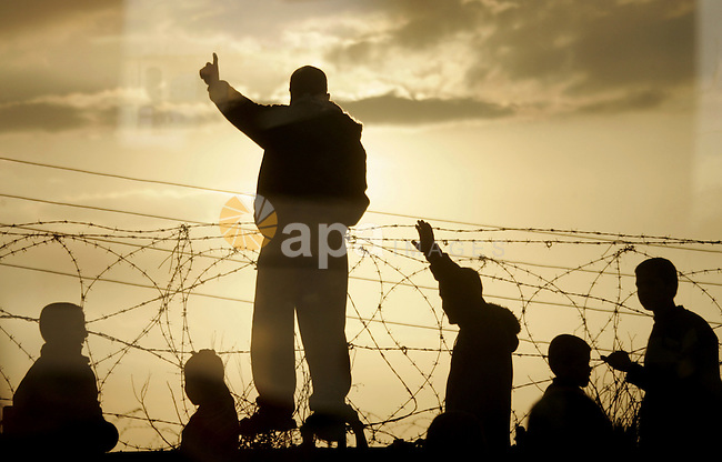 A picture took from the car glass window as Palestinians take part in a protest near the border between the Gaza Strip and Egypt on December 31, 2009 against the underground barrier Egypt is building along its border with the Gaza Strip. Egypt has only implicitly confirmed the construction of the underground wall, which was first reported by Israeli media, saying it is aimed at shutting down the extensive network of smuggling tunnels along the border. Photo by Abed Rahim Khatib