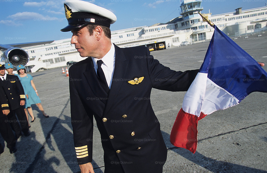 """John Travolta, captain and pilot, of his own jumbo jet, with the french flag, at Le  Bourget airport together with his plane and crew...John Travolta is pilot of his very own jumbo jet, a 1964 Boeing 707-100 series. In 2003, John Travolta flew his jumbo jet around the world, in partnership with Quantas, to rekindle confidence in commercial aviation, and to remind us that elegance and style are a part of flying. The crew are dressed in tailor made authentic uniforms from the Quantas museum. The men's uniforms are styled on British Naval uniforms and the ladies' designed by Chanel. His jumbo jet sports a personalised number plate N707JT which speaks for itself. The aircraft is named """"Jett Clipper Ella"""" dedicated to his son and daughter. This jumbo together with his other aircraft are housed in purpose built hangars at his home in Florida, USA."""