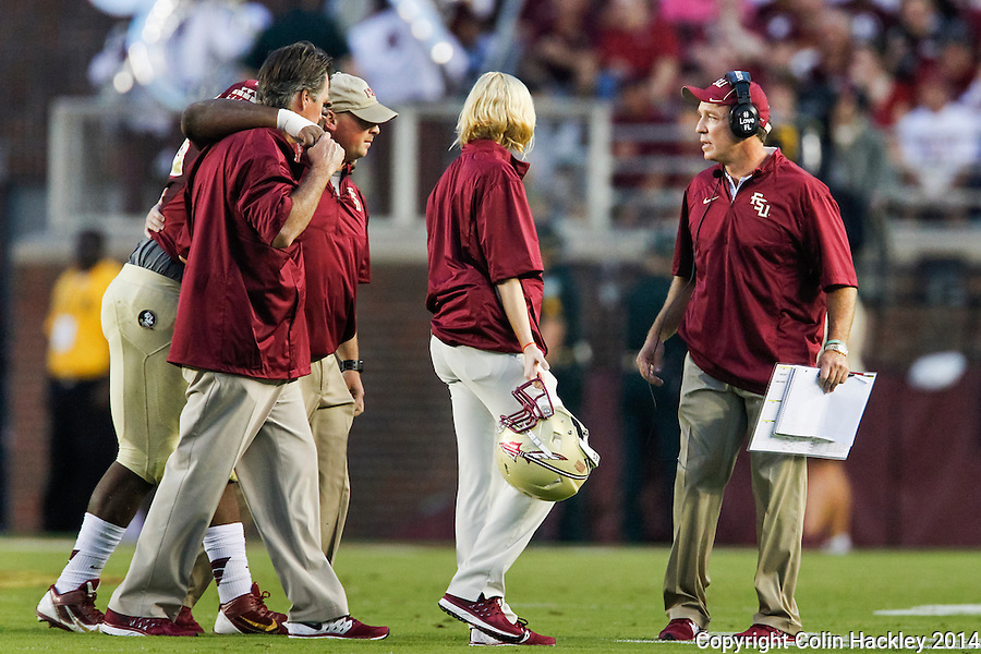 TALLAHASSEE, FL 9/6/14-FSU-CITADEL-Florida State's Head Coach Jimbo Fisher, right, checks on Eddie Goldman as he is helped from the field during first half action against the Citadel Sept. 6, 2014 at Doak Campbell Stadium in Tallahassee. Goldman was one of three defensive lineman injured during the game.<br />