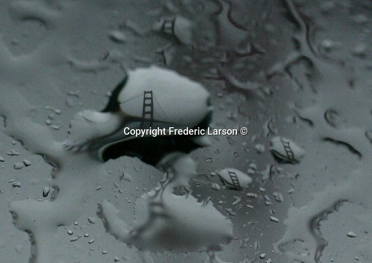Rain drops reflect the Golden Gate Bridge on a car window in San Francisco, California.