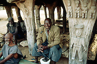 "Mali. Province of Mopti. Koporo-Pen. Dogon land. 20 km away from the bottom of the Bandiagara cliff.  Village life. Old men sit in  the ""Tougouna"" which is traditionnaly used by elders for reunion. The Tougouna's wood pillars are decorated with symbolic sculture from the dogon art. © 2003 Didier Ruef"