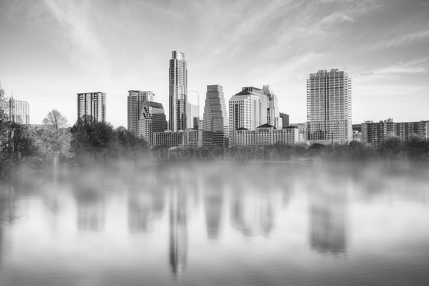 This black and white images shows the Austin skyline from Lady Bird Lake on a late January day.
