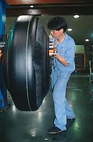 """China. Province of Zhejiang. Hangzhou. Hangzhou Zhongce Rubber Co., Ltd. A worker checks the rubber's quality on a production line for the type"""" All Steel Trucks Tyres"""".  © 2004 Didier Ruef"""