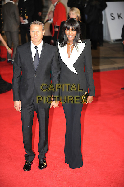 Vyacheslav Doronin & Naomi Campbell.Royal World Premiere of 'Skyfall' held at the Royal Albert Hall, London, England..October 23rd, 2012.full length white black suit blazer lapels clutch bag holding hands couple .CAP/CAS.©Bob Cass/Capital Pictures.
