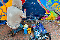 A Colombian hooded artist paints graffiti on the wall in La Candelaria, Bogota, 10 July 2010.
