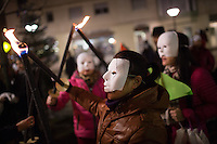 Women of Chinese descent concealed by masks, representing  sex workers in Paris, light flames as they take part in a demonstration on the International Day to End Violence Against Sex Workers at Place Jean Rostand. Chinese sex workers in Paris, who are usually here without legal papers, often experience violence and harassment on the streets from clients and even police. Paris, France. Dec. 17, 2014