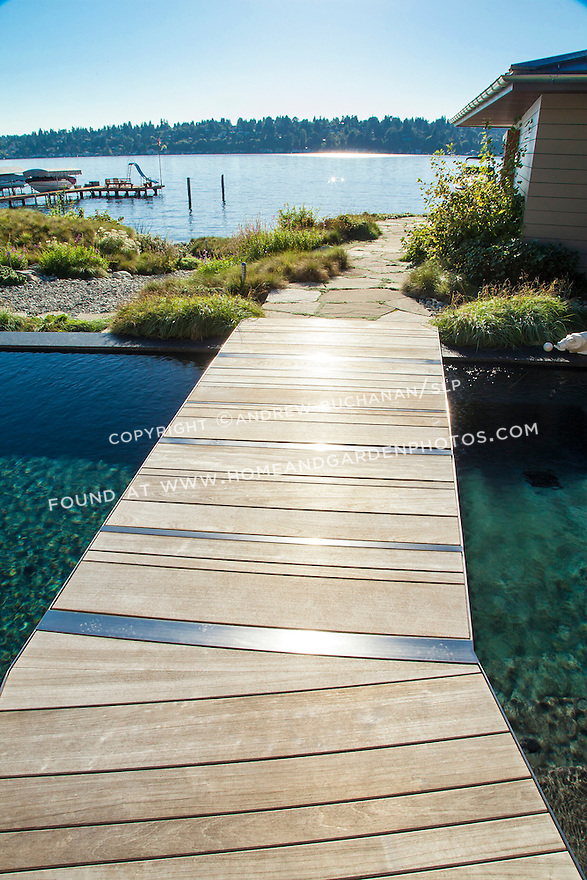 An angled bridge leads across the end of a swimming pool in a Seattle-area home.