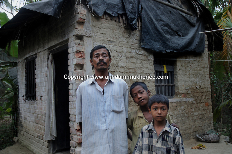 Alamgir with his father Sk. Jahirul and his youngest brother Abdulla during one of his visit to home. He ran away from home  6 years ago due to domestic violence and poverty. As per his version his father was a drunkard and used to beat his mother for no reason. His father even could not earn enough money to buy food for their big family. Due to this traumatic situation he ran away from house at the age of seven. Ever since, the Sealdah railway station in Kolkata has been his home. As far as company is concerned, he had not much reason to miss his family. There are around 500 children, from 5 to 16 years, who live in the premises of Kolkata's second largest train terminus. Most of them addicted to Brown Sugar and sniffing industrial adhesive Dendrite. They say they don't feel hungry if they take the drugs. Their presence is conspicuous, even in a place that registers an average footfall of 1.4 million on weekdays. Their activities cover a wide range, from begging, to pulling handcarts, to petty theft, to selling odds and ends on the platform or on trains. The money, earned or ill-gotten as the case may be, is spent in procuring heroin, brown sugar, cocaine, and tubes of Dendrite. Calcutta, West Bengal, India. Arindam Mukherjee