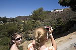Two girls wearing sunglasses take a picture of the Hollywood Sign, Hollywood, Los Angeles, CA