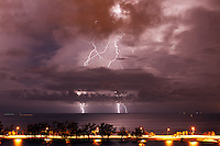 Cloud-to-ground lightning strikes the southern side of Biscayne Bay during a nocturnal thunderstorm in Miami, Florida. Rickenbacker Causeway is visible in the foreground.