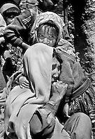 Qamar Habibulla with one of her eight children in the ruins of a house in Aqrabat, Aghanistan on Thursday, June 27, 2002. Her husband and two of her children were killed when the family had to flee the Taliban attack on her home village of Saighan in 2001. 46 ethnic Hazara widows and their children live in Aqrabat. More than six million people fled Afghanistan during the years of conflict following the Soviet invasion in 1979.