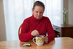 Mature woman sitting at dining room table with tea reflecting with worried look on face