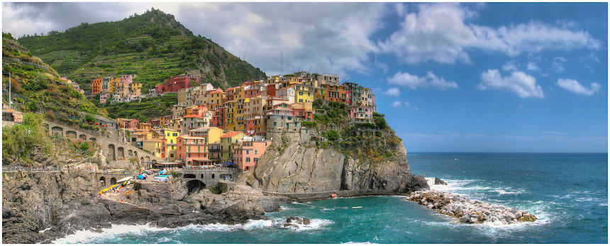 The Cinque Terre is one of my favorite places in the world. I backed through Italy after college and found myself falling in love with these magical fishing villages perched along the rocky coast of Italy. This image of Manarola is a panorama and a view of a typical summer afternoon. The five villages of the Cinque Terre now depend mainly on tourism, wine, and fishing for their existence. However, if you can visit in the off season, you'll find you have the area to yourself, along with the locals. And you might even be invited to try homemade wine in a cellar like we were on one visit in March.