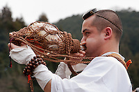 A yamabushi or mountain priest blows into a conch shell at the Hi Watari firewalking festival, Takaosan guchi near Tokyo, Japan. Sunday March 8th 2009