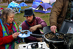Camp Dignity residents Jada Mae Langloss and John Paul Cupp share a meal around the cook stove. They are members of a small community in which people work together under a strict set of rules so none goes without.