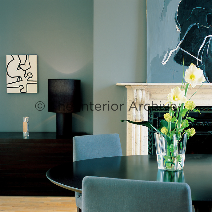 A dining room with a traditional fireplace and furnished in a contemporary way with a black lacquer table by Eero Saarinen and classic upholstered dining chairs. The cabinet and lamp are by Minott. The paintings are by contemporary Irish artists.
