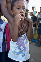 Philippines. Province Eastern Samar. Hernani. Barangay (neighbourhood) Batang. A boy holds his father's hands in his hands. The son wears a white t-shirt of the Avengers based on the Marvel Comics superhero team. Their house was destroyed by typhoon Haiyan's winds and storm surge. Typhoon Haiyan, known as Typhoon Yolanda in the Philippines, was an exceptionally powerful tropical cyclone that devastated the Philippines. Haiyan is also the strongest storm recorded at landfall in terms of wind speed. Typhoon Haiyan's casualties and destructions occured during a powerful storm surge, an offshore rise of water associated with a low pressure weather system. Storm surges are caused primarily by high winds pushing on the ocean's surface. The wind causes the water to pile up higher than the ordinary sea level. 24.11.13 © 2013 Didier Ruef