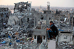 A Palestinian man sits on the rubble of destroyed houses after returning home in the Tufah neighbourhood in eastern Gaza City on August 31, 2014. Calm returned to the coastal enclave in a August 26 ceasefire, and Gazans were gradually starting to rebuild their lives after a bloody and destructive 50-day war, the deadliest for years.. Photo by Ashraf Amra