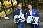 Foto: VidiPhoto<br /> <br /> RHENEN -  De twee panda's die volgend jaar naar het Ouwehands Dierenpark in Rhenen komen heten Wu Wen (het vrouwtje) en Xing Ya (het mannetje). Dat heeft eigenaar Marcel Boekhoorn van de dierentuin dinsdag onthuld. Tijdens het staatsbezoek van koning Willem-Alexander en koningin Maxima aan China, maakten de Chinezen bekend twee panda's aan Nederland uit te lenen. De hoop is dat het paar in de dierentuin in Rhenen voor nakomelingen van de bedreigde diersoort gaat zorgen. De naam Wu Wen betekent in het Nederlands 'mooie krachtige wolk', Xing Ya staat voor 'elegante ster'. Er zijn volgens het dierenpark nog veel voorbereidingen nodig voordat de panda's naar Nederland kunnen komen. De bouw van het verblijf start binnenkort en moet volgend jaar herfst klaar zijn. Ook moeten pandaverzorgers worden opgeleid. Chinese experts zullen het proces begeleiden en volgen. Ze zullen ook regelmatig langskomen. De verwachting is ook dat de komst van de dieren veel extra publiek zal trekken. Ouwehands gaat vooralsnog uit van een maximum van 10.000 bezoekers per dag. Vanwege de hoge kosten van het onderhoud van de dieren zal de toegangsprijs ook iets omhoog gaan. Het is nog niet bekend hoeveel. De parkeergelegenheid zal ook worden uitgebreid. Ouwehands moet voor de dieren een miljoen euro per jaar betalen aan China. Dit geld komt ten goede aan de bescherming van de zwart witte beren in het wild. De twee panda's kennen elkaar nog niet. De beesten gaan 'daten' voordat ze samen gaan leven in hun nieuwe onderkomen in Rhenen, wat Pandasia gaat heten.  Ouwehands heeft een bamboebedrijf in Asten gevonden dat twee keer per week verse bamboe gaat leveren. Een panda eet ruim vijftig kilo bamboe per dag. Foto: Manager dierverzorging Dirk-Jan van der Kolk (l) en directeur Robin de Lange tonen de foto's van de twee reuzenpanda's op de plek waar ze straks komen. Nu nog het verblijf van de pelikanen.