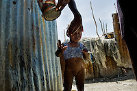 A Haitian woman washes her baby girl with wastewater in the slum of Cité Soleil, Port-au-Prince, Haiti, 16 July 2008. Cité Soleil is considered one of the worst slums in the Americas, most of its 300.000 residents live in extreme poverty. Children and single mothers predominate in the population. Social and living conditions in the slum are a human tragedy. There is no running water, no sewers and no electricity. Public services virtually do not exist - there are no stores, no hospitals or schools, no urban infrastructure. In spite of this fact, a rent must be payed even in all shacks made from rusty metal sheets. Infectious diseases are widely spread as garbage disposal does not exist in Cité Soleil. Violence is common, armed gangs operate throughout the slum.