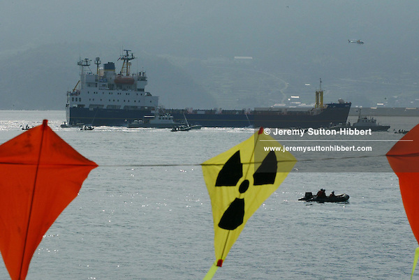 SURROUNDED BY JAPANESE POLICE AND COAST GUARD GREENPEACE INFLATABLES &quot;PROTEST&quot; ( bear witness...), WITH KITES FROM THE ARCTIC SUNRISE GREENPEACE SHIP, IN UCHIURA BAY, BESIDE THE TAKAHAMA NUCEAR PLANT, AS BNFL SHIP 'PACIFIC PINTAIL' DEPARTS LATE AFTERNOON AFTER COLLECTING REJECTED PLUTONIUM MOX FUEL, FOR SHIPMENT BACK TO THE UNITED KINGDOM. TAKAHAMA, JAPAN. 04/07/02. .PIC &copy; JEREMY SUTTON-HIBBERT/GREENPEACE 2002..*****ALL RIGHTS RESERVED. RIGHTS FOR ONWARD TRANSMISSION OF ANY IMAGE OR FILE IS NOT GRANTED OR IMPLIED. CHANGING COPYRIGHT INFORMATION IS ILLEGAL AS SPECIFIED IN THE COPYRIGHT, DESIGN AND PATENTS ACT 1988. THE ARTIST HAS ASSERTED HIS MORAL RIGHTS. *******