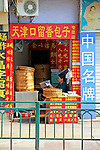 Asia, China, Chongqing. A shopkeeper reads a newspaper.