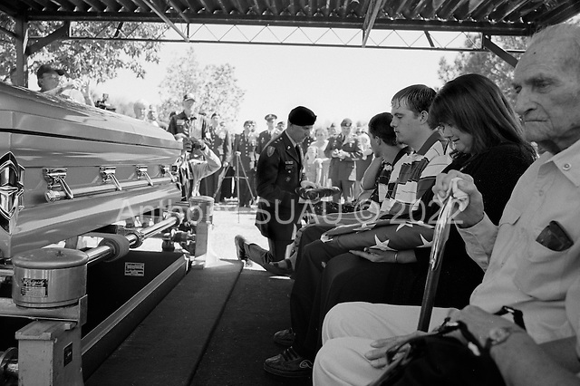 Tucson, Arizona.USA.March 16, 2007..At the Evergreen Cemetery Lori Kasson, the widow of Staff Sgt. Darrel D. Kasson, 43, of Florence, Arizona with her three children (to her right) Jeremy (19), Dale (15), daughter Lisa Varnes (22), and (to her left) grandfather Leo at the funeral services for her husband. The mother Sheron Jones is given a flag in military honors. She is handed the flag from his coffin in military honors. He died March 4 in Tikrit, Iraq, of wounds suffered when an improvised explosive device detonated near his vehicle at Bayji, Iraq. He was assigned to the 259th Security Forces Company, Phoenix.