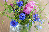 Posy bunch of pretty attractive pastel pink and blue spring and summer flowers, a rustic floral bouquet arrangement in glass vase