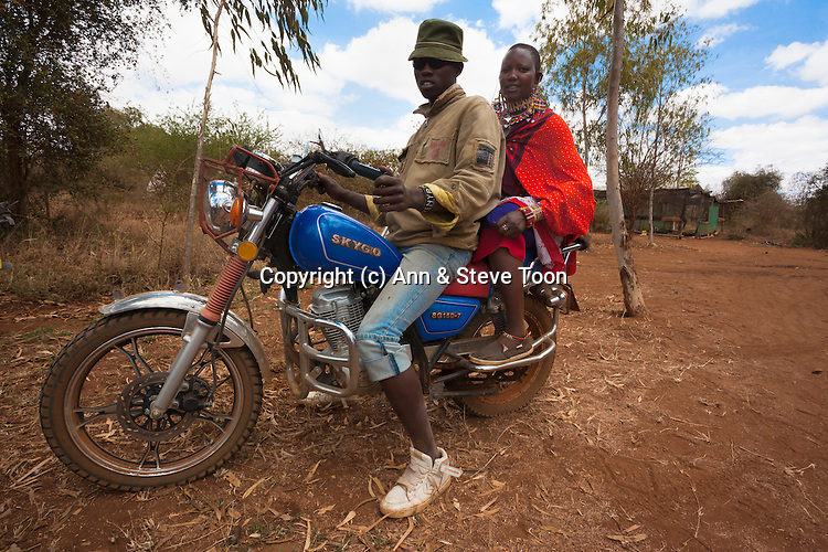 Maasai couple arriving by motorbike at the Predator Compensation Fund Pay Day, Mbirikani Group Ranch, Amboseli-Tsavo eco-system, Kenya, Africa, October 2012