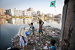 Despite the congested traffic and lack of space, Dhaka is a magnet for millions of Bangladeshis. Korail Slum is largest settlement of rootless people in the city (population estimate of 120,000). It lies on the opposite side of Banani Lake overlooking Gulshan, the residential neighborhood where some of the country's wealthiest families live.<br /> <br /> The slum has no permanent sanitation or sewage facilities, thus residents construct toilettes on bamboo stilts over Banani Lake (more like a pond than a lake). Children bathe and play in the sewage infested waters of the small lake.<br /> <br /> The shore is lined up with trash, but its one of the few open spots where children can fly their kites in their informal settlement.<br /> <br /> March 2011. Gabriela Barnuevo
