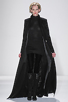 Model walks runway in a black loro piana cashmere sculpted coat w/top-stitching +beaded t-medallion lining, black handloomed cashemere/silk ribbed turtleneck tunic+velvet leggings, from the Zang Toi Fall 2012 &quot;Glamour At Gstaad&quot; collection, during Mercedes-Benz Fashion Week New York Fall 2012 at Lincoln Center.