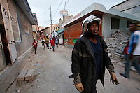 Firefighter Will Mondesir heads to an apartment fire in Port-au-Prince, Haiti. Heavy traffic and narrow streets prevented the crew from getting its water truck to a blaze at a two-story home, so the owners had to put it out themselves with water buckets. A few dozen under-equipped firefighters are tasked with providing fire service to a damaged city of over two million people.