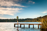 Woman looking from Lake Ianthe jetty at sunset, South Westland, West Coast, New Zealand