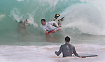 During a wave a camera man films a boarder at Sandy Beach in Hawaii during high-tide.