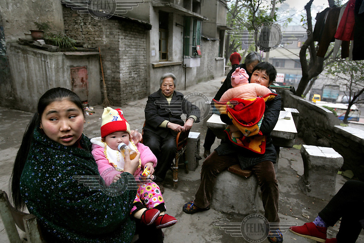A family of migrant workers sit chatting in the street.  Every year millions of rural dwellers migrate to cities seeking work in order to send wages back to support their families.  They return to their communities for a family reunion once a year to celebrate Chinese New Year together..