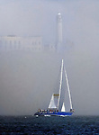 A sail boat sails past Alcatraz Island on San Francisco Bay, California.