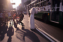 Gays have fun and enjoy street Carnival. Banda de Ipanema ( Ipanema band ), Rio de Janeiro, Brazil. Gay dressed as bride gives a flower to bus passenger.