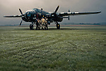 B-25 Mitchell WWII bomber and crew at dawn on grass runway