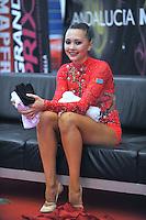 """Anna Alyabyeva of Kazakhstan smiles at """"kiss & cry""""  during event finals  at 2010 Grand Prix Marbella at San Pedro Alcantara, Spain on May 16, 2010. Anna placed 6th AA at Marbella 2010. (Photo by Tom Theobald)."""