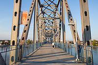 A woman walks on the walkway on the Junction Bridge on the Arkansas River Trail in Little Rock, Arkansas.