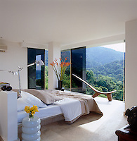 The guest bedroom is furnished with an African chair and a built-in concrete bed and has a spectacular view of the jungle