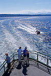 Passengers on Ferry boat crossing Puget Sound with  Olympic Mountains on a sunny day with coast guard escort Seattle Washington State USA.