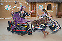 Rajasthani dancers in traditional costumes performing in desert camp in front of mud huts; Rajasthan, India --- Model Released