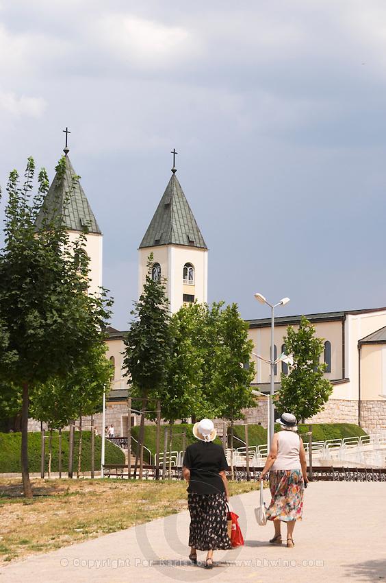 The church, two old ladies in sun hats and flowery skirts. Medugorje pilgrimage village, near Mostar. Medjugorje. Federation Bosne i Hercegovine. Bosnia Herzegovina, Europe.