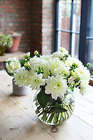 Detail of a simple flower arrangement in a glass vase on Kally Ellis's kitchen table