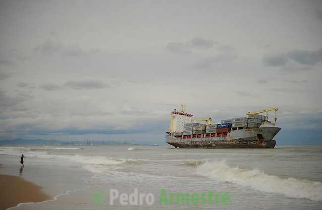 A Spanish Coast Guard patrol boat and an helicopter attempt to rescue two cargo ships that ran aground at Saler beach near Valencia on September 29, 2012 after a heavy storm. At least eight people, including a young girl and an elderly woman, have died in Spain as a result of floods brought on by downpours, regional officials said. Four people died in the Andalusia region, including a woman in her 80s, a couple found in their car and a man who died of a heart attack. Some 500 people remained evacuated from their homes in the area early on Saturday after the torrential rains caused rivers to break their banks and flooded roads and railways, regional authorities said. (c) Pedro ARMESTRE